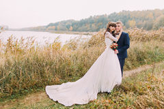Portrait of beautiful newlywed young couple outdoors. Happy groom posing with his bride on riverside Royalty Free Stock Photography