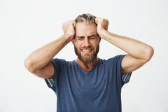 Portrait of beautiful nordic guy with trendy haircut and beard holding head with hands suffering from headache after a. Long day at work royalty free stock image