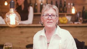 Portrait of a beautiful old lady sitting at a table in a bar and talking to the camera. Old woman with eyeglasses stock footage