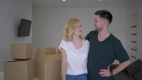 Portrait of beautiful pair new home owners show keys to apartment and hug while relocation on background of boxes stock footage
