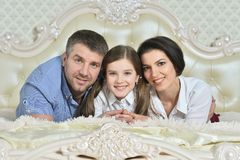 Portrait of a beautiful parents and daughter posing in room stock photo