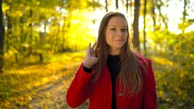 Portrait of a beautiful pensive girl in a red coat with a yellow maple leaf in the background in the autumn forest stock video footage