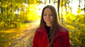 Portrait of a beautiful pensive girl in a red coat with a yellow maple leaf in the background in the autumn forest. Portrait of a beautiful dreamy girl in a red stock footage