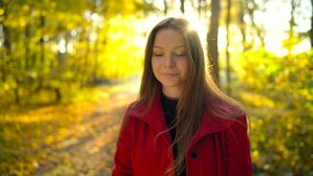 Portrait of a beautiful pensive girl in a red coat with a yellow maple leaf in the background in the autumn forest. Slow stock video footage