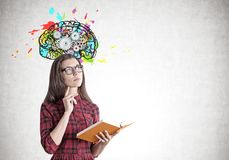 Young woman in a dress with a book, brain, gears Stock Photos