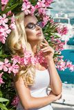 Portrait beautiful phenomenal stunning elegant sexy blonde model woman with perfect face wearing a glasses stands with elegant out Royalty Free Stock Photo