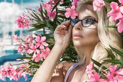 Portrait beautiful phenomenal stunning elegant sexy blonde model woman with perfect face wearing a glasses stands with elegant out Stock Photo