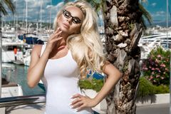 Portrait beautiful phenomenal stunning elegant sexy blonde model woman with perfect face wearing a glasses stands with elegant sui Stock Image