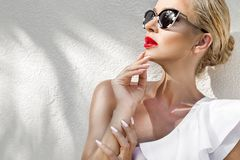 Portrait beautiful phenomenal stunning elegant blonde model woman with perfect face wearing a sunglasses. Stands with elegant swinsuit on amazing view with palm stock photo