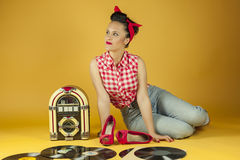 Portrait beautiful pin up listening to music on an old jukebox r Stock Photography