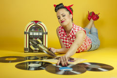 Portrait beautiful pin up listening to music on an old jukebox r Royalty Free Stock Photo