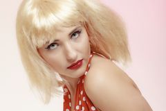 Portrait beautiful pinup girl in blond wig retro red dress. Vintage. Royalty Free Stock Photo