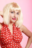 Portrait beautiful pinup girl in blond wig retro red dress. Vintage. Royalty Free Stock Photography