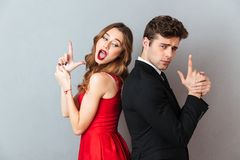 Portrait of a beautiful playful couple dressed in formal wear. Standing back to back and showing gun gesture over gray wall background Stock Photo