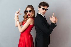 Portrait of a beautiful playful couple dressed in formal wear. And sunglasses standing back to back and showing gun gesture over gray wall background Royalty Free Stock Photo