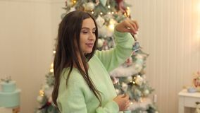 Portrait of a pregnant girl near a Christmas tree. Portrait of a beautiful pregnant girl with Christmas toy in the hands against the background of the Christmas stock footage