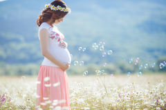 Portrait of beautiful pregnant woman in field blowing bubbles stock photo