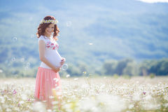 Portrait of beautiful pregnant woman in field blowing bubbles Royalty Free Stock Image