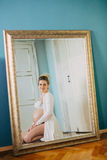Portrait of a beautiful pregnant woman in front of a mirror at home Stock Photos