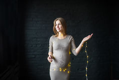 Portrait of a beautiful pregnant woman with illumination in the studio on a black brick background.  Royalty Free Stock Image