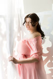 Portrait of beautiful pregnant woman opening curtains on window Royalty Free Stock Photography