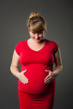 Portrait of beautiful pregnant woman in red dress Stock Image