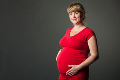 Portrait of beautiful pregnant woman in red dress Royalty Free Stock Images