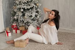 Portrait of beautiful pregnant woman tree Christmas new year gifts stock photo