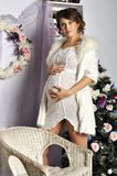Portrait of the beautiful pregnant young woman near a Christmas tree Stock Images