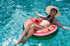 Portrait Beautiful Pretty woman girl plays watermelon ring buoy. In swimming pool blue water stock images