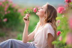 Beautiful young girl is wearing casual clothes having rest in a garden with pink blossom roses. Portrait of beautiful pretty woman with makeup is walking near Royalty Free Stock Photography