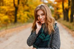 Portrait of a beautiful pretty young attractive woman with blue eyes with a sweet smile in a stylish coat with a scarf. On the background of golden leaves in stock photography