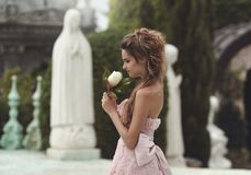 Portrait of a Beautiful Princess in a pink dress with a flower the Magnolia . a blonde with long hair walks through the