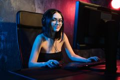 Portrait of the beautiful professional gamer girl playing in online video game, casual cute geek wearing glasses, talks. And chats with her teammates and royalty free stock images