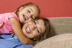 Portrait of beautiful real mother and daughter hugging Royalty Free Stock Photos