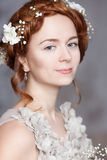 Portrait of beautiful red-haired bride. She has a perfect pale skin with delicate blush. White flowers in her hair. She smiles gently. She has light gray eyes Royalty Free Stock Photo
