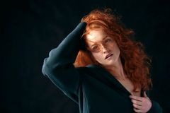 Portrait of a beautiful red-haired curly-haired girl on a black background
