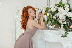 Portrait of a beautiful red-haired girl with blue eyes holding w Royalty Free Stock Images