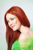 Portrait of beautiful red-haired girl with flower painted on his face Stock Photography