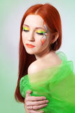 Portrait of beautiful red-haired girl with flower painted on his face Royalty Free Stock Photo