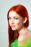 Portrait of beautiful red-haired girl with flower painted on his face Stock Image