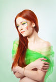 Portrait of beautiful red-haired girl with flower painted on his face Stock Photo