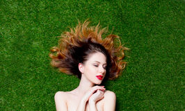 Portrait of beautiful red-haired girl on green grass. Stock Images