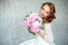 Portrait of beautiful red-haired girl holding bouquet. Royalty Free Stock Image