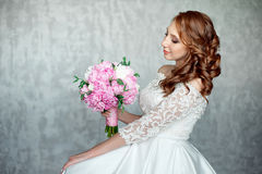 Portrait of beautiful red-haired girl holding bouquet. Stock Photos