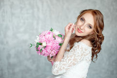 Portrait of beautiful red-haired girl holding bouquet. Stock Photography