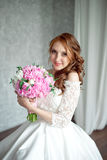 Portrait of beautiful red-haired girl holding bouquet. Stock Photo
