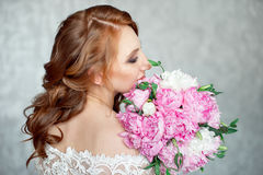 Portrait of beautiful red-haired girl holding bouquet. Royalty Free Stock Images