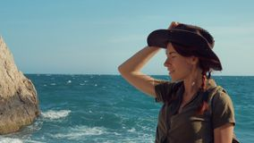 Portrait of a beautiful red-haired traveler girl in a cowboy hat on the sea beach. stock video