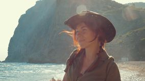Portrait of a beautiful red-haired traveler girl in a cowboy hat on the sea beach. Slow motion stock video footage